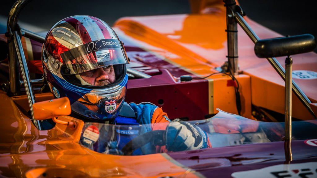 race driver checks mirror in Pit Lane