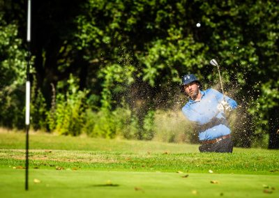 golfer against green bushes background