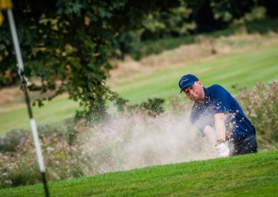 golfer plays out of bunker