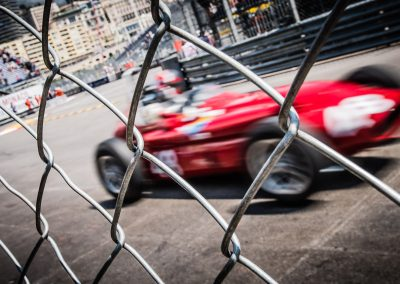 red historic f1 car behind fence