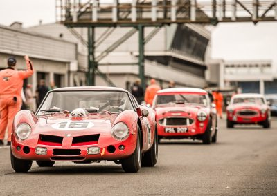 3 red classic racing cars in pit lane