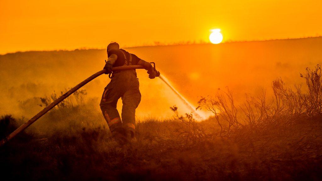 Firefighter drags hoses